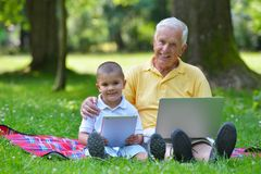 Abuelo y niño que usa el ordenador portátil Fotos de archivo libres de regalías