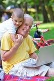 Abuelo y niño que usa el ordenador portátil Imagen de archivo