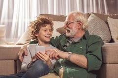 Abuelo y niño sonrientes que guardan el teléfono imagenes de archivo