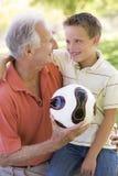 Abuelo y nieto al aire libre con la bola Imagen de archivo libre de regalías