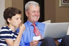 Abuelo y nieto con el ordenador portátil Imagen de archivo libre de regalías