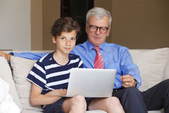 Abuelo y nieto con el ordenador portátil Fotos de archivo libres de regalías