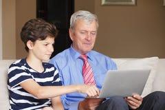 Abuelo y nieto con el ordenador portátil Imágenes de archivo libres de regalías