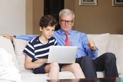 Abuelo y nieto con el ordenador portátil Fotografía de archivo libre de regalías