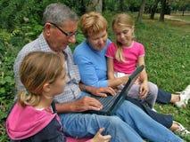 Abuelo y nieto de los gemelos con la computadora portátil
