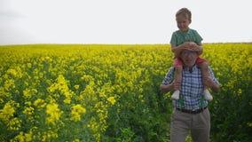 Abuelo y nieto durante paseo a través del campo almacen de video