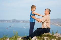Abuelo y nieto en la cima de la montaña. Imagenes de archivo