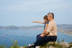 Abuelo y nieto en la cima de la montaña. Foto de archivo