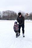 Abuelo y nieto en la pista de patinaje Fotos de archivo