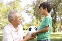 Abuelo y nieto en parque con el balompié Foto de archivo libre de regalías