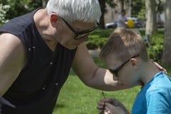 Abuelo y nieto en un paseo común en el parque imagen de archivo