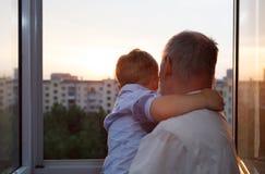 Abuelo y nieto que abrazan en el balcón Imagen de archivo libre de regalías