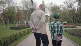 Abuelo y nieto que caminan en el parque con sus partes posteriores a la c?mara Ambas personas tienen sus manos detr?s de sus part almacen de video