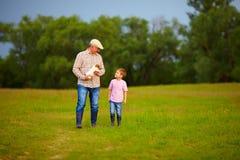 Abuelo y nieto que caminan a través del campo verde, con el perrito en manos Fotografía de archivo