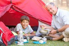 Abuelo y nieto que cocinan el desayuno en acampada foto de archivo