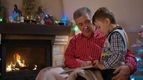Abuelo y nieto que leen un libro metrajes