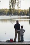 Abuelo y nieto que pescan apagado de muelle en el lago Foto de archivo libre de regalías