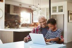 Abuelo y nieto que se sientan alrededor de la tabla en casa usando el ordenador portátil junto foto de archivo libre de regalías