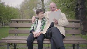 Abuelo y nieto que se sientan en el parque en el banco, viejo hombre que lee el libro para el muchacho Concepto de las generacion almacen de video