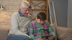 Abuelo y nieto que se sientan en el sofá usando la tableta y que miran la cámara Comodidad casera, idilio de la familia almacen de metraje de vídeo