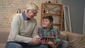 Abuelo y nieto que se sientan en el sofá usando una tableta que mira uno a, sonriendo Comodidad casera, idilio de la familia almacen de video