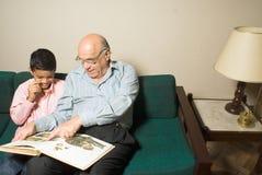 Abuelo y nieto que sientan un sofá-Hori fotos de archivo