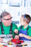 Abuelo y nieto que usa el multímetro foto de archivo libre de regalías