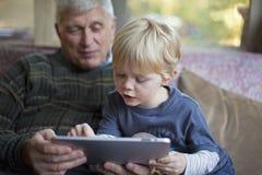 Abuelo y nieto que usa la PC de la tablilla Fotografía de archivo libre de regalías