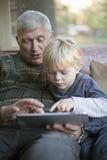 Abuelo y nieto que usa la PC de la tablilla Imagen de archivo
