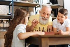 Abuelo y nieto sonrientes que hacen un rompecabezas junto Imagen de archivo libre de regalías