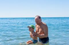 Abuelo y nieto sonrientes que juegan el mar Imagen de archivo libre de regalías