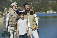 Abuelo y nietos con las cañas de pescar por el lago Foto de archivo