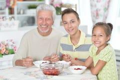 Abuelo y nietos que comen las fresas frescas en el kitch fotografía de archivo libre de regalías