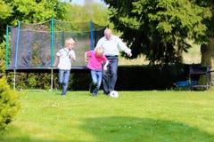 Abuelo y nietos que juegan a fútbol en el jardín Fotografía de archivo libre de regalías