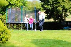 Abuelo y nietos que juegan a fútbol en el jardín Imagen de archivo libre de regalías