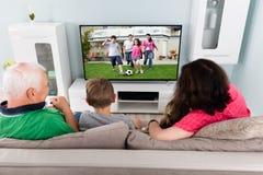 Abuelo y nietos que miran la televisión junto Imágenes de archivo libres de regalías
