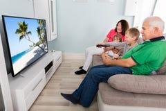 Abuelo y nietos que miran la televisión junto Fotografía de archivo