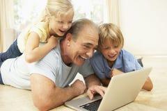 Abuelo y nietos que usan la computadora portátil en el país Foto de archivo libre de regalías