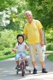 Abuelo y niño felices en parque Imagen de archivo