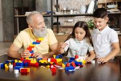 Abuelo y sus nietos que montan un sistema de la nueva construcción Imagen de archivo libre de regalías