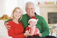 Abuelos con el bebé en el equipo de Santa Fotografía de archivo