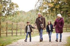 Abuelos con los nietos en Autumn Walk In Countryside Together fotos de archivo