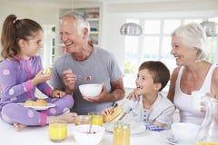 Abuelos con los nietos que comen el desayuno en cocina Foto de archivo libre de regalías