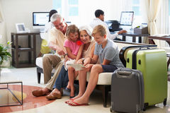 Abuelos con los nietos que llegan en pasillo del hotel Imágenes de archivo libres de regalías