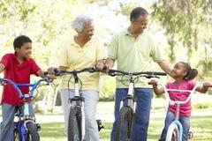 Abuelos con los nietos que montan las bicis Imágenes de archivo libres de regalías