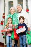 Abuelos con los nietos y los regalos en la Navidad Imagenes de archivo
