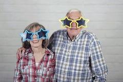 Abuelos divertidos con los vidrios grandes de la estrella foto de archivo