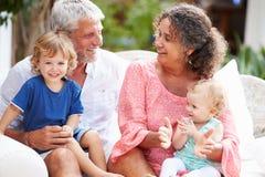 Abuelos en casa que se sientan al aire libre con los nietos foto de archivo libre de regalías