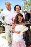 Abuelos hispánicos y nieta que comprueban el buzón fotografía de archivo