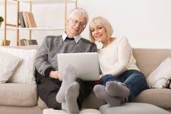 Abuelos modernos Pares mayores websurfing en el ordenador port?til foto de archivo libre de regalías